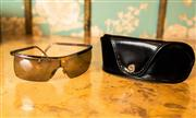 Sale 8577 - Lot 147 - A pair of Salvatore Ferragamo sunglasses featuring a gun metal finish with logo name engraving and original case, Condition: Very Good