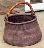 Sale 9060H - Lot 13 - A woven basket with a leather bound handle. Diameter 50cm
