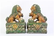 Sale 8815C - Lot 2 - Pair of Chinese Ming style sancai glazed Buddhist Lions, in mirror reverse, each clutching a ball on one paw above a double lotus pe...