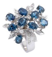 Sale 8928 - Lot 371 - A VINTAGE SAPPHIRE AND DIAMOND COCKTAIL RING; floral spray design set with 9 oval cut fine blue sapphires and 17 single cut diamonds...