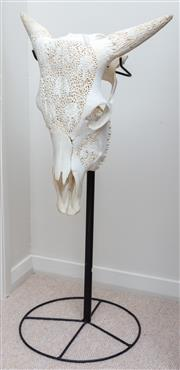 Sale 9066H - Lot 57 - A carved and blanched cow skull on an iron stand. Total height 80cm.