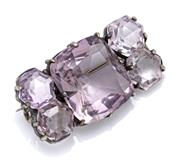 Sale 9083 - Lot 474 - A VINTAGE AMETHYST BROOCH; centring an approx. 19ct cushion cut amethyst surrounded by 4 hexagonal cut amethysts totalling approx. 1...