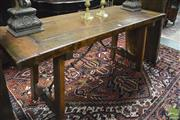 Sale 8359 - Lot 1034 - A Spanish Style Guard Room Style Walnut Table with thick panel top and splayed legs with wrought iron braces.