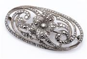 Sale 9015J - Lot 81 - A vintage sterling silver and marcasite brooch C: 1940's, the scroll pierced oval panel centered by a flower L: 60mm