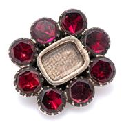 Sale 9083 - Lot 354 - A GEORGIAN GARNET LOCKET BROOCH; cut down claw set with 8 foil back garnets around a central locket compartment in rose gold plate,...