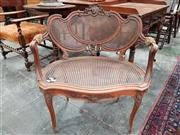 Sale 8728 - Lot 1024 - Louis XV Style Carved Walnut Generous Armchair, with rocaille and caned back & seat, the arms padded & on cabriole legs