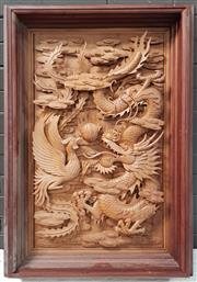 Sale 8956 - Lot 1027 - A Well Carved Chinese Fruitwood Panel of a swirling dragon and phoenix chasing a pearl mounted in a deep cedar frame - repair to clo...