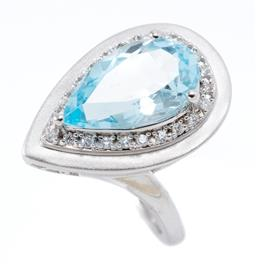 Sale 9169 - Lot 392 - A SILVER TOPAZ AND STONE SET COCKTAIL RING; featuring a pear cut blue topaz within a border of 26 round cut zirconias, top 26 x 15mm...