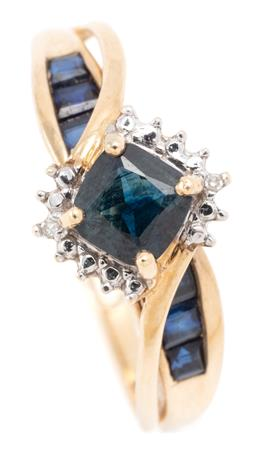 Sale 9128J - Lot 35 - A 9CT GOLD SAPPHIRE AND DIAMOND RING; claw set with a modified square cut dark blue sapphire and 2 single cut diamonds above split b...