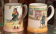 Sale 8926K - Lot 33 - Two Royal Doulton mugs with Dickens scene and Únder the Greenwood Tree, H 12cm