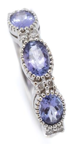 Sale 9054 - Lot 400 - AN 18CT WHITE GOLD TANZANITE AND DIAMOND RING; half hoop millegrain set with 3 oval tanzanites totalling approx. 1.50ct adjacent to...