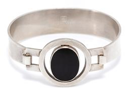 Sale 9168J - Lot 317 - A SILVER STONE SET BANGLE BY DESIGN PER; centring a 20 x 16mm oval onyx plaque to 28mm halo surround to S clasp, internal circ. 17cm...