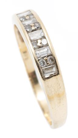 Sale 9182 - Lot 348 - A 9CT GOLD DIAMOND BAND; channel set with 5 baguette cut and 8 round brilliant cut diamonds, width 4mm, size O, wt. 1.63g.
