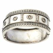 Sale 8315 - Lot 325 - A LATE 19TH CENTURY SILVER HINGED CUFF BANGLE; front with applied fleur de lis border (some losses), internal size 4.5 x 5.5cm, widt...