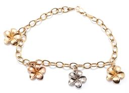 Sale 9160 - Lot 378 - A 14CT THREE TONE GOLD FLORAL CHARM BRACELET; 5mm wide trace link chain to parrot clasp attached with 4 frangipani charms in yellow,...