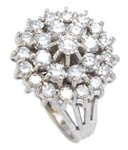 Sale 8915 - Lot 382 - AN 18CT WHITE GOLD DIAMOND CLUSTER RING; centring a round brilliant cut diamond of approx. 0.14ct claw set above a double surround o...