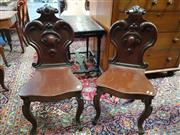 Sale 8792 - Lot 1093 - Pair of Victorian Mahogany Hall Chairs, with heavy carved & scrolled backs & raised on cabriole legs