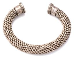 Sale 9132 - Lot 563 - A HEAVY SILVER TRIBAL TORQUE BANGLE; 14mm wide plaited design to flat terminals with wire twist decoration, diam. 71mm, wt. 184.25g.
