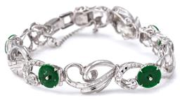 Sale 9124 - Lot 526 - A JADE AND DIAMOND BRACELET; 11mm wide engraved scrolling links set with nephrite jade discs in rhodium plated silver to snap lock c...