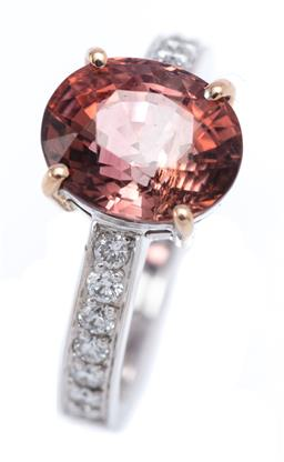 Sale 9191H - Lot 68 - AN 18CT WHITE GOLD TOURMALINE AND DIAMOND RING; featuring an oval cut cinamon tourmaline of 3.91ct between upswept shoulders each se...