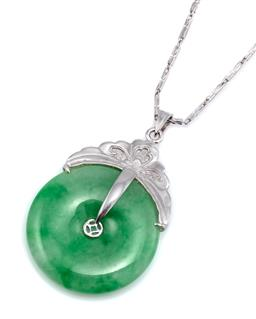 Sale 9124 - Lot 524 - A GOLD AND PLATINUM JADE PENDANT NECKLACE; 26mm round green jadeite jade bi disc with 18ct white gold fittings and flower engraved s...