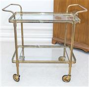 Sale 8402H - Lot 45 - A brass and glass drinks trolley on castors.