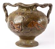 Sale 9083N - Lot 32 - An art nouveau two handled metal vase decorated with nudes amidst grapevine. Height 31cm.
