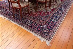 Sale 9190H - Lot 179 - A large woollen Persian Isfahan rug with red floral medallion on cream ground with blue border, 412cm x 305cm