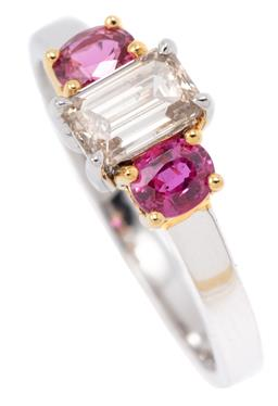 Sale 9149 - Lot 449 - AN 18CT WHITE GOLD RUBY AND DIAMOND RING; centring an emerald cut diamond of approx. 0.71ct adjacent to 2 oval cut rubies totalling...