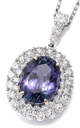Sale 9124 - Lot 397 - A TANZANITE AND DIAMOND CLUSTER PENDANT NECKLACE; centring an oval cut tanzanite of approx. 5ct to double surround of 40 round brill...