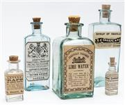 Sale 9054E - Lot 10 - Five early glass bottles with paper labels for : Syrup of Squills, Lime water, Tincture of Mastich, Curaped and Japanese toothache d...