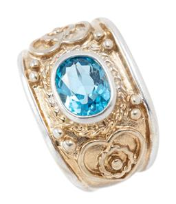 Sale 9169 - Lot 366 - A SILVER BLUE TOPAZ RING; 15.3mm wide ring with decorative gilt top rub set with an oval cut blue topaz of approx. 2.18ct, size N ,...