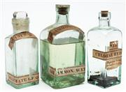 Sale 9054E - Lot 13 - A group of three glass chemist bottles with paper labels and lids, including Ammonia, Sulphate of quinine and Chloral hydrate.
