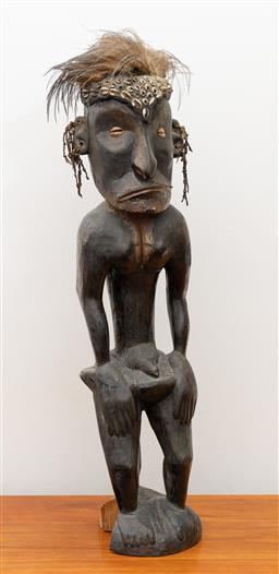 Sale 9239H - Lot 46 - A carved timber tribal figure with cowrie shell eyes and feathers, H75cm.