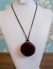 Sale 8577 - Lot 176 - A burgundy rabbit fur ball necklace with black leather strap and brass hoop, L 49cm, Condition: NEW