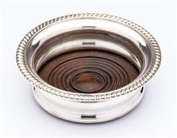 Sale 9087H - Lot 279 - A good antique English silverplate large bottle coaster, C: 1900, fitted with a mahogany base with concentric turned rings D: 14.5cm