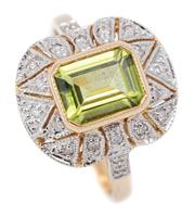 Sale 9083 - Lot 401 - A DECO STYLE PERIDOT AND DIAMOND RING; rub set with an emerald cut peridot of approx. 2.30ct to surround and shoulders set with 20 r...