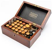 Sale 9054E - Lot 17 - A mahogany hinged box by Ashton & Parson, Homeppathic medicine manufacturers London, containing 26 miniature bottles and a measuring...