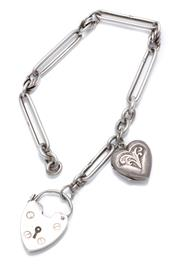 Sale 8974 - Lot 320 - AN ANTIQUE SILVER PADLOCK BRACELET; fetter and fancy link attached with a silver front and back heart shape locket charm to an heart...