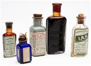 Sale 9054E - Lot 18 - A group of five small glass bottles both clear and coloured, all bearing paper labels to include: Quineine, Depilatory,