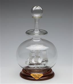 Sale 9253 - Lot 89 - A commemorative display decanter holding an art glass frigate - timber stands plaque reading: Golden Hind, 16th Century (H:30cm)
