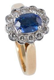 Sale 8974 - Lot 388 - AN 18CT GOLD SAPPHIRE AND DIAMOND CLUSTER RING; centring a fine blue oval cut sapphire of approx. 1.1ct surrounded by 12 round brill...