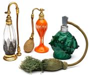 Sale 9054E - Lot 27 - Three vintage perfume bottles with puff sprayers including a Czechoslovakian deco green glass, an orange glass of waisted form and o...