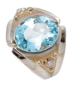 Sale 9221 - Lot 311 - A TWO TONE SILVER TOPAZ RING; rub set with an oval cut blue topaz of approx. 5.48ct to gilt top set with 2 round cut zirconias to ta...
