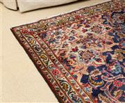 Sale 8550H - Lot 68 - A large Persian woollen rug with central medallion and repeating floral pattern on royal blue ground, 318 x 227cm
