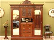 Sale 8925H - Lot 41 - An antique walnut mirrored four door wardrobe, with fine carved decoration. Separates into five parts, Height 241cm (with crest), Wi...