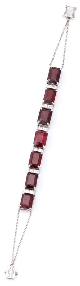 Sale 9124 - Lot 499 - A PLATINUM RUBY AND DIAMOND BRACELET; claw set with 7 emerald cut glass treated rubies (each approx 10 x 7.5mm) to 6 uniting links e...