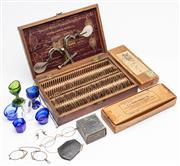 Sale 9054E - Lot 32 - A mahogany box by the Spencer Opthalmic Manufacturing Co with steel tester, lenses, assorted glasses and pince nez, eyebaths and car...