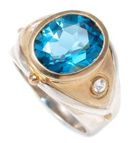 Sale 9164J - Lot 318 - A TWO TONE SILVER TOPAZ RING; set with an oval cut blue topaz of approx. 5.48ct to gilt top set with 2 round cut zirconias to taperi