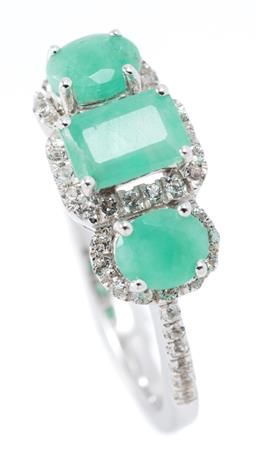 Sale 9169 - Lot 387 - A SILVER EMERALD AND GEMSET RING set with an emerald cut emerald surrounded by 19 round cut zirconias flanked by 2 oval cut emeralds...
